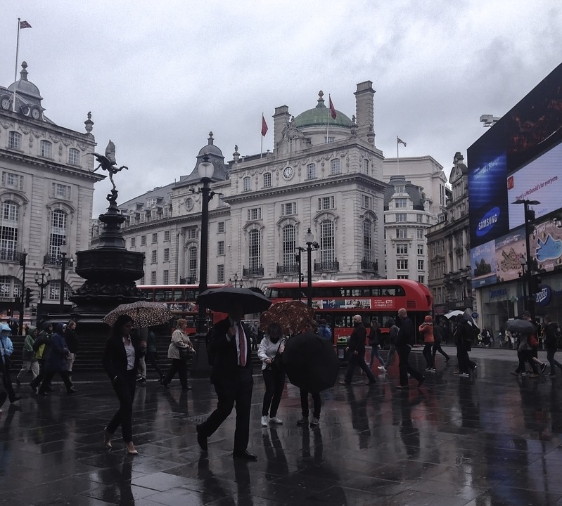 Rain in London, lots of people with umbrellas, red bus in the background (Central London, England, UK)