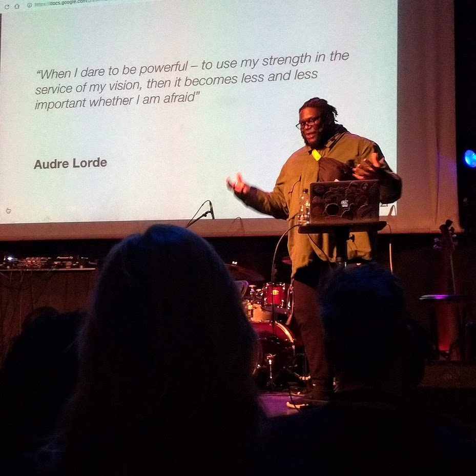 Alex Fefegha appears in front of a slide that reads: 'When I dare to be powerdul - to use my strength in the service of my vision, then it becomes less and less important whether I am afraid.' Audre Lorde