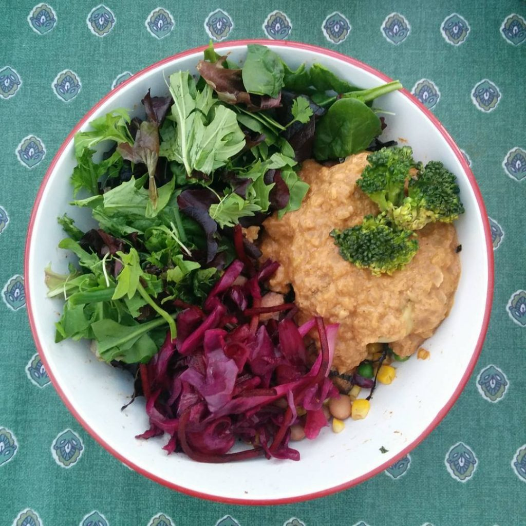 Bowl containing mixed salad leaves, red coleslaw and a thick peanut butter stew, with a couple of kernels of sweetcorn and peas