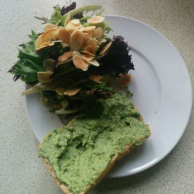 two slices of toast, one spread with a light green pesto spread, the other topped with mixed salad leaves and toasted flaked almonds