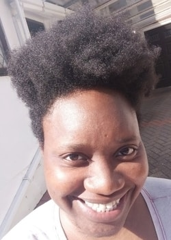 LiLi smiling in September sun with a beautiful afro
