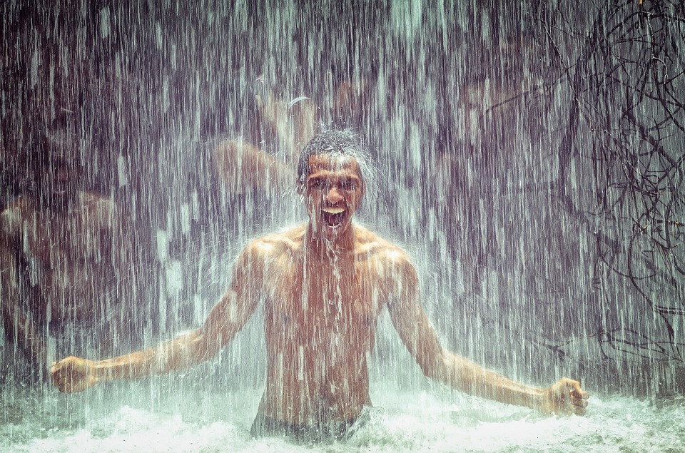 Black person under a refreshing and expansive waterfall, they have a huge grin on their face with arms wide and fists clenched