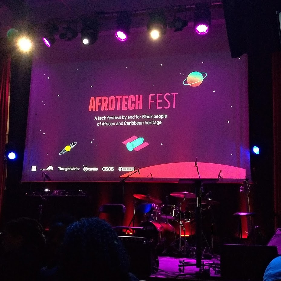 Opening slide that reads 'Afrotech Fest: A tech festival by and for Black people of African and Caribbean heritage'. On an illustrated space background with colourful planets and satellites. Sponsor logos appear at the bottom of the slide, but they're fuzzy and not legible in the photo