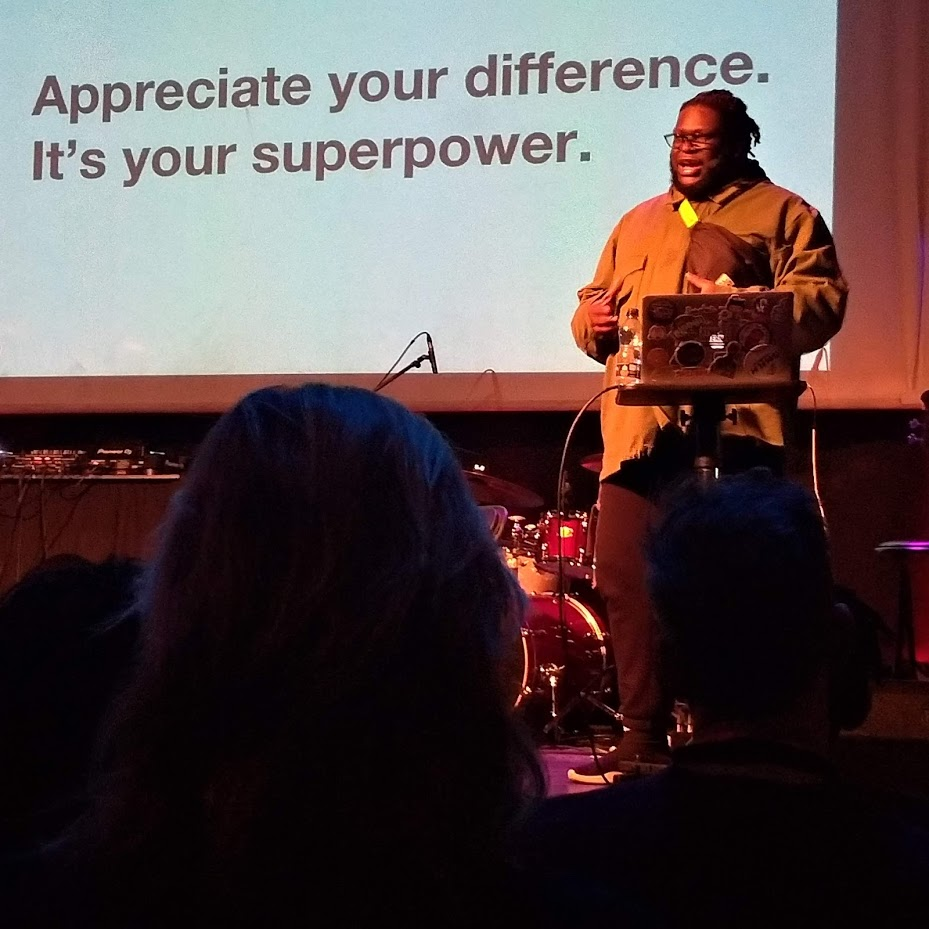 Alex Fefegha appears in front of a slide that reads: Appreciate your difference. It's your superpower.