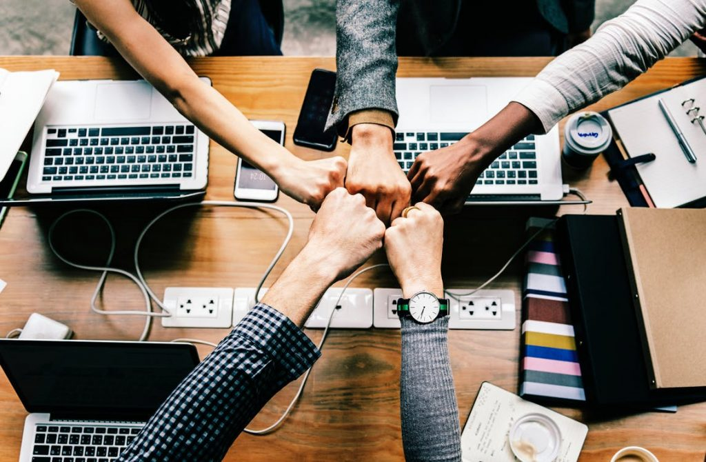 Fist bump of 5 fists, over a table with laptops open, mobile phones out, notebooks... Camaraderie in the office, connected to colleagues who are physically located elsewhere