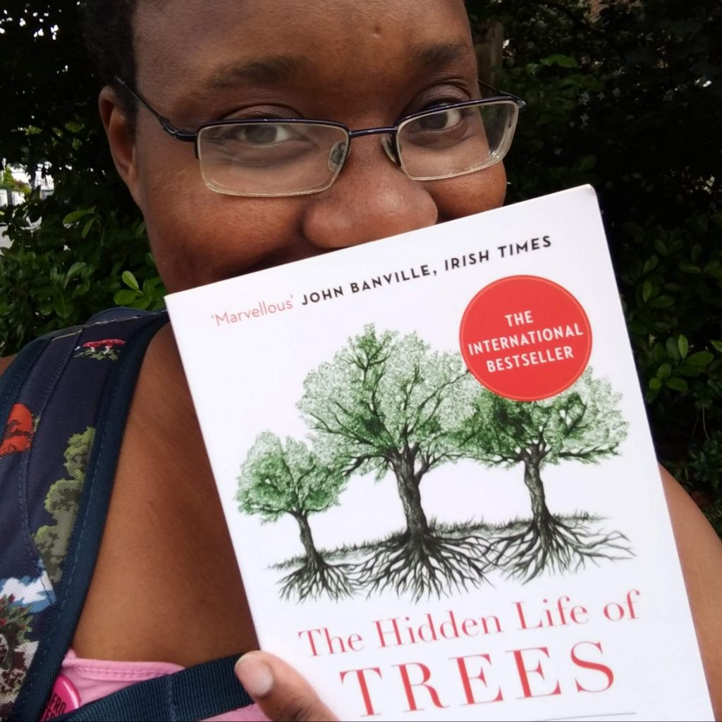 LiLi smiles behind The Hidden Life of Trees book