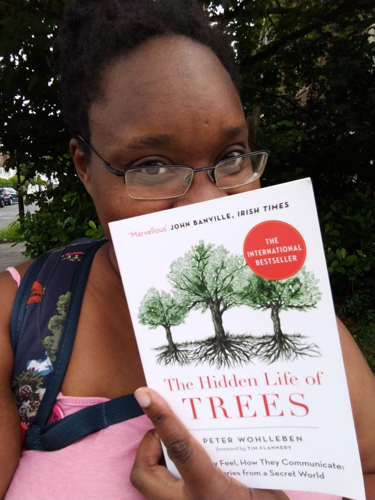 LiLi hiding behind The Hidden Life of Trees book