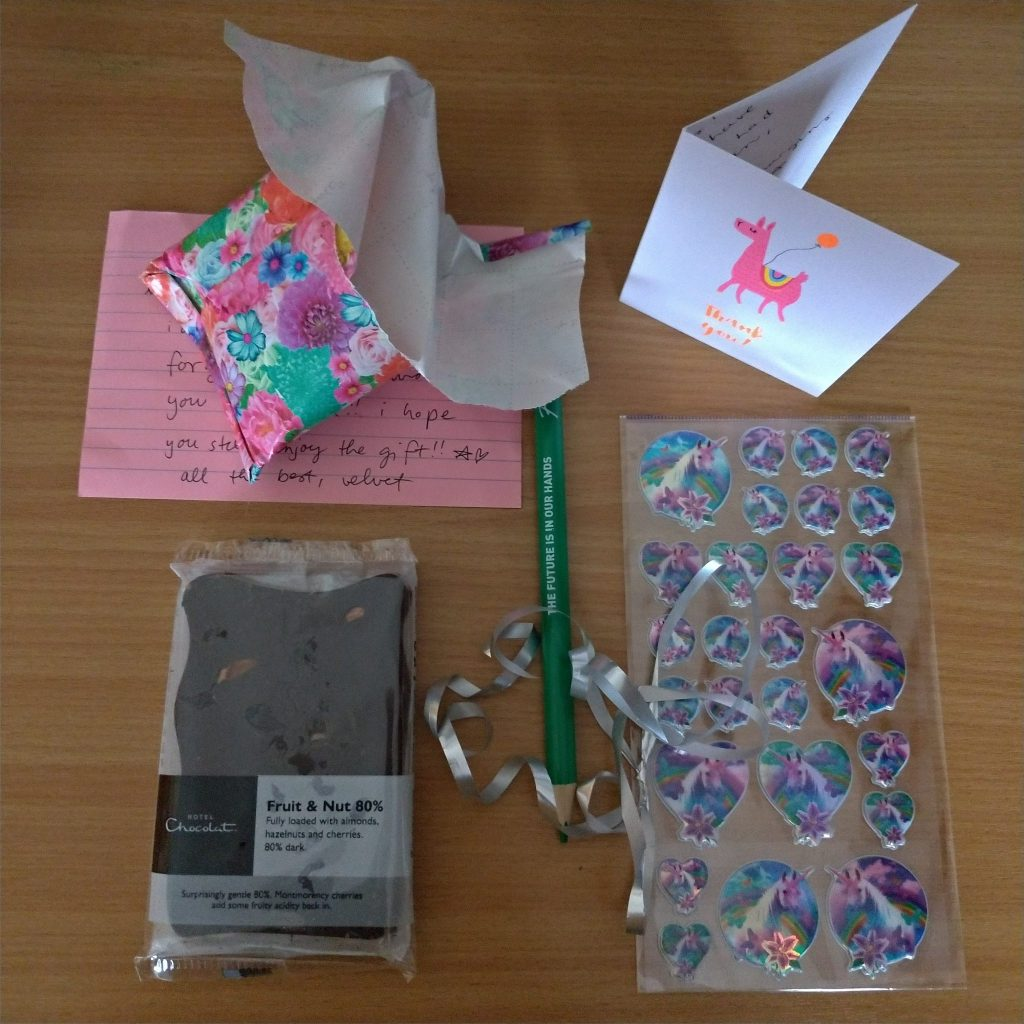 unicorn stickers, fancy chocolate, a green pencil and an adorable pink llama thank you card, just unwrapped