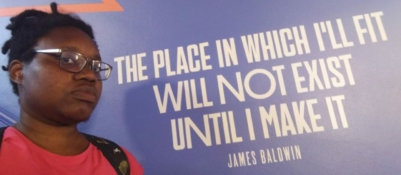 "LiLi, defiant, next to a James Baldwin quote: ""The place in which I'll fit will not exist until I make it."""