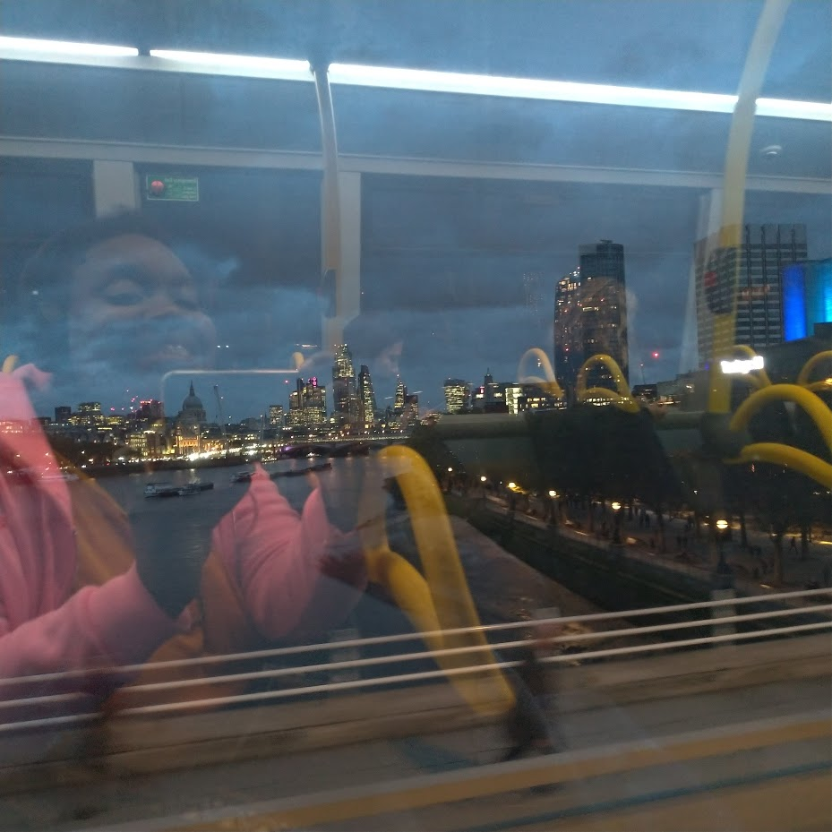 LiLi's reflection smiling in a bus window, view of London at night over the river outside