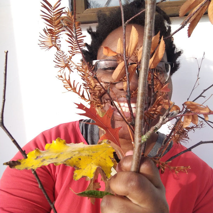LiLi grinning broadly, holding up a collection of branches, twigs and autumn leaves