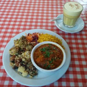 Rich tomato curry with potato salad, shredded carrots & beetroot, golden rice, and turmeric latte