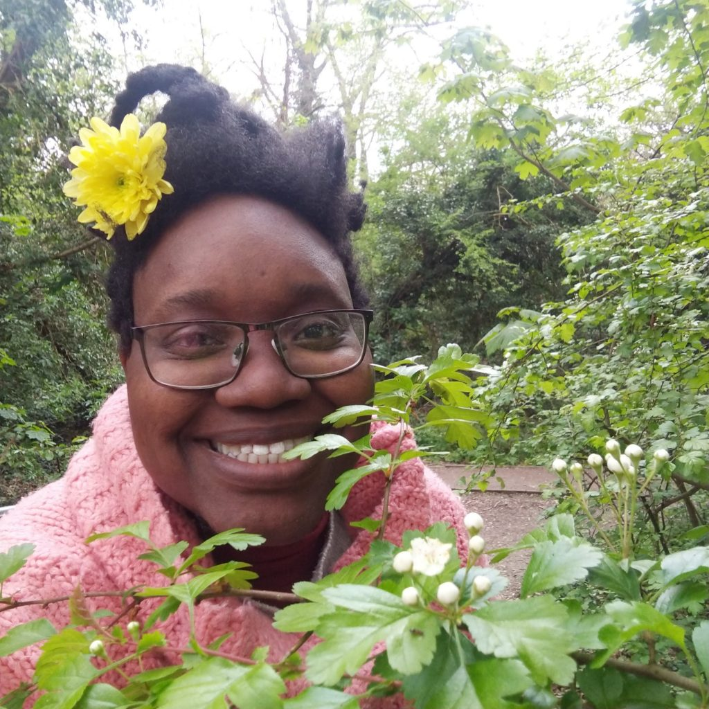 LiLi is smiling with a yellow chrysanthemum in their hair, in front of them are flowering hawthorns