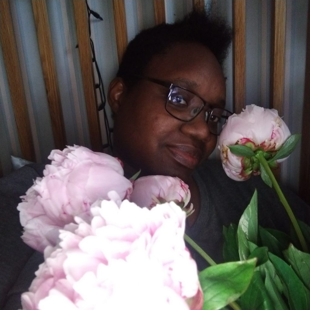 LiLi holding a bouquet of rose pink peonies and smiling into the camera.