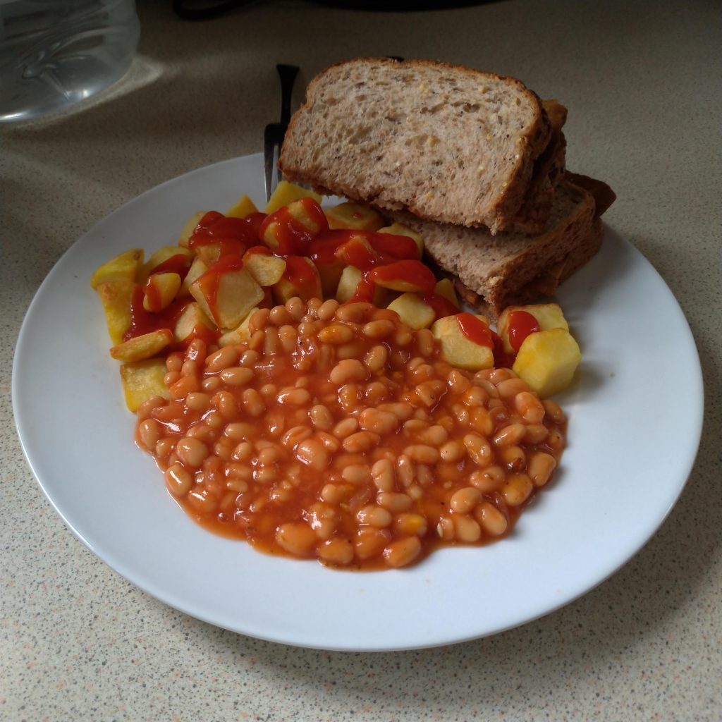 Plate of baked beans, chipped potatoes, vegan bacon sandwiches and ketchup.
