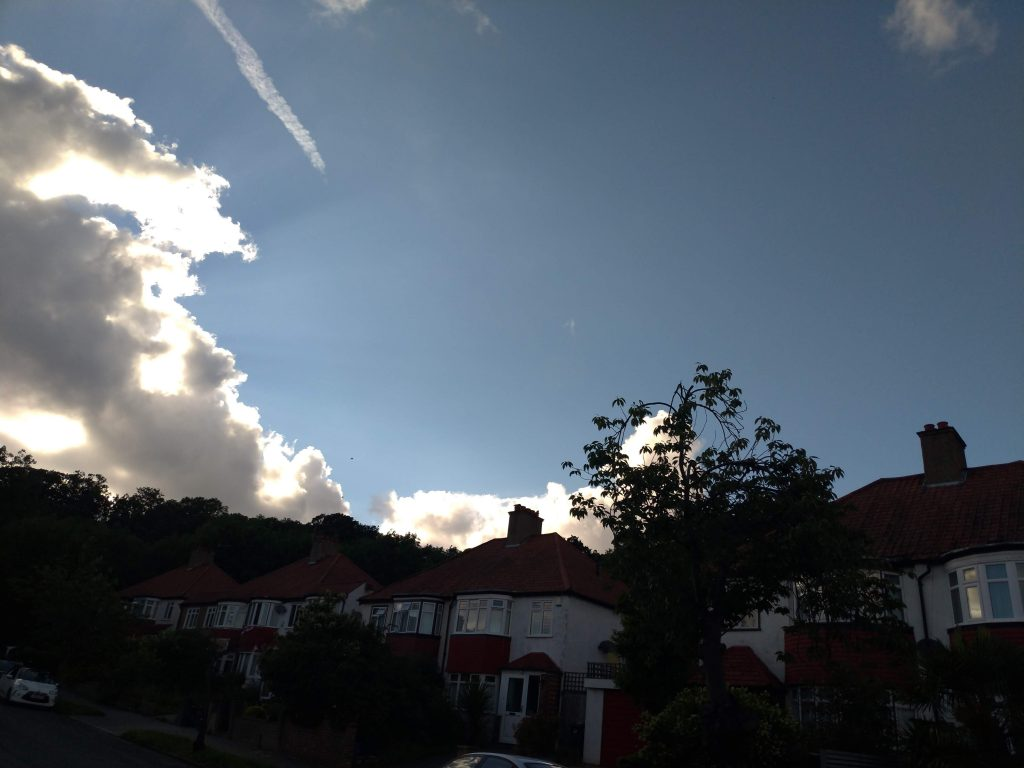 Expanse of blue sky - a break in the heavy grey clouds, tinged at their edges with such a bright light they're almost glowing. Cherry tree silhouette against the sky. Terraced houses in the background.