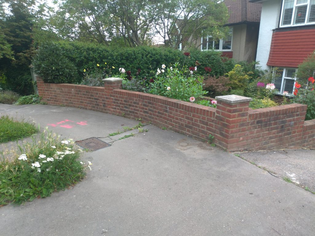 a red brick wall curves around a grey pavement between a grass verge full of flowering yarrow and a garden of dahlias in different colours