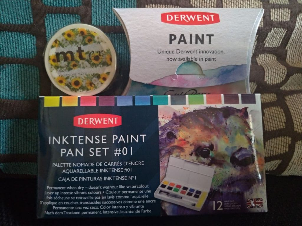 Paint travel set and extra paint pans, new in their packaging, a role off sunflower-adorned washi tape