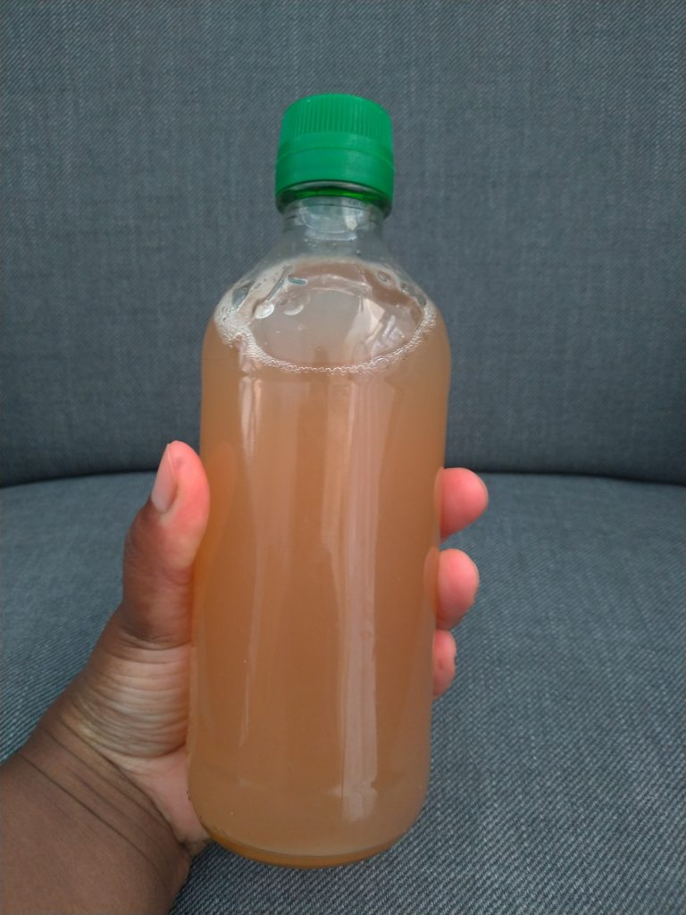 Bottle full of a rosy-peach liquid.
