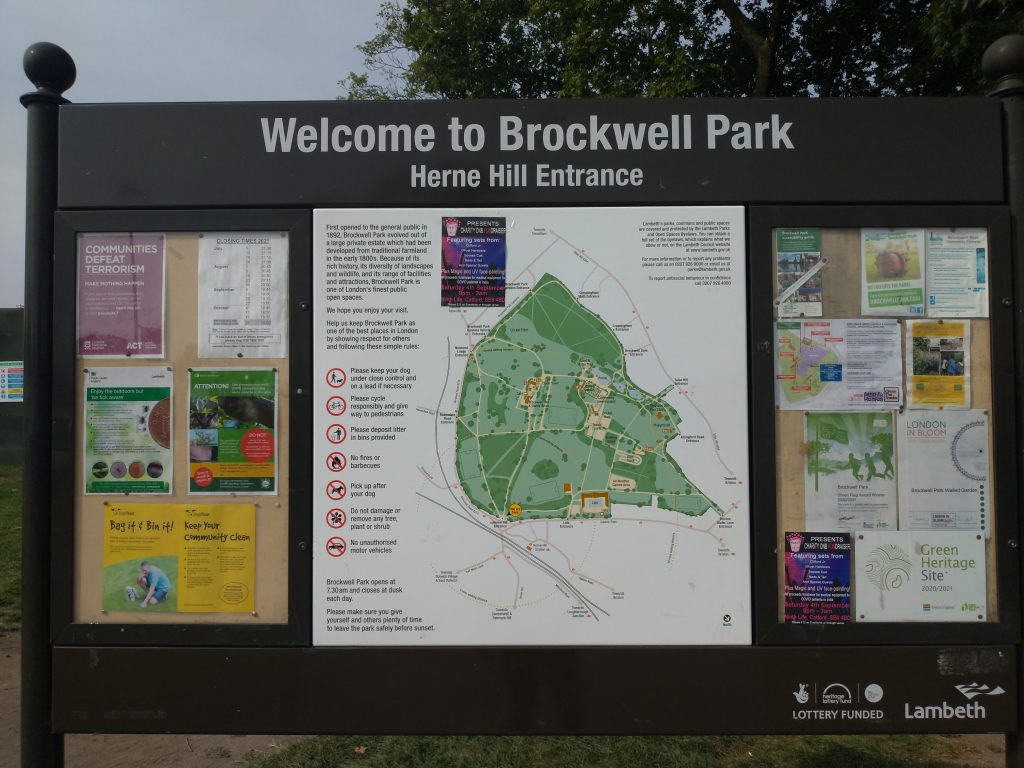 Welcome to Brockwell Park: Herne Hill Entrance sign, with a map of the map and trees in the background.